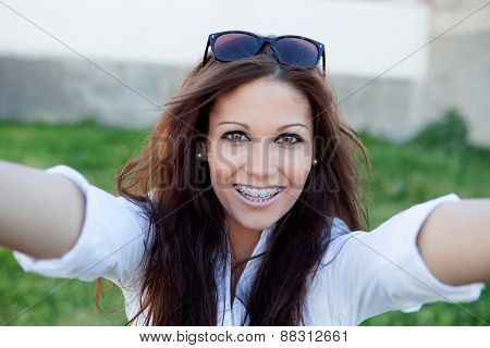 Pretty brunette in the park by becoming a photo with mobile