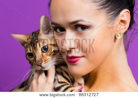 Young attractive woman holding a Bengal cat