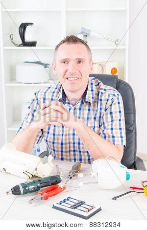Smiling man at home appliance service workshop