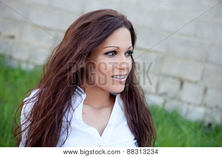 Brunette cool girl with brackets relaxed in the park