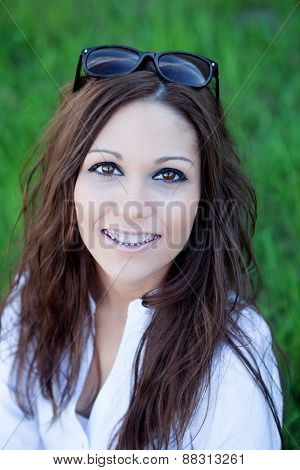 Brunette cool girl with brackets in the park