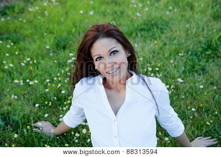 Brunette cool girl with brackets sitting on the grass with many daisies