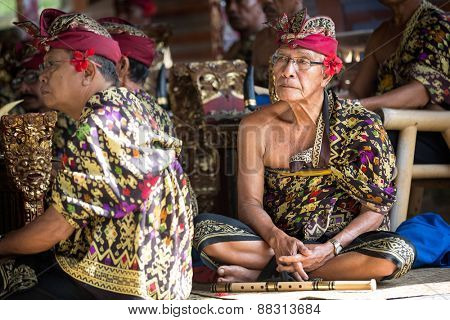 BALI, INDONESIA, DECEMBER, 24,2014: senior musician sitting on floor with his  group musicians who  play traditional Balinese music for Barong Dance show on December 24, 2014 in Bali, Indonesia