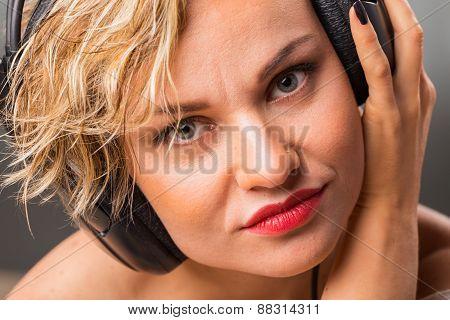 Cute blonde girl posing in the studio headphones . Beautiful blue eyes