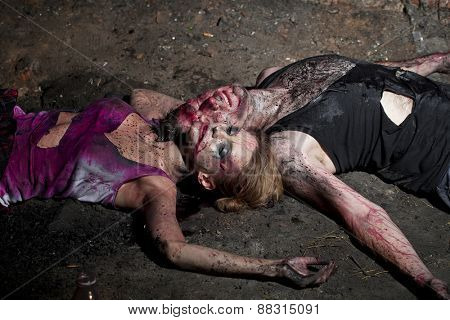 Couple of bloody man and woman lying on the ground