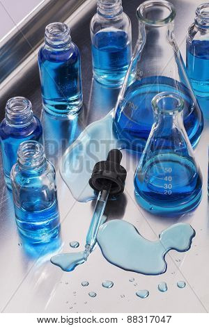 Laboratory Glassware and spilled test fluid with dropper