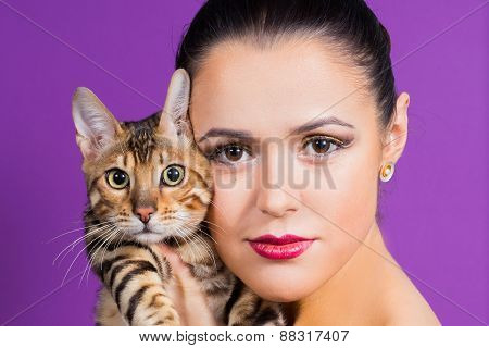 Cute brunette girl holding a Bengal cat, girl posing in the studio