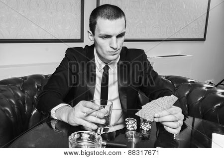 Poker player in the casino with glass of whiskey and cards at the gaming table.