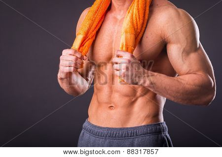 Healthy muscular young man after a workout on dark background