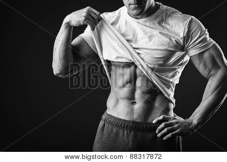 Muscular man bodybuilder. Man posing on a black background, poster