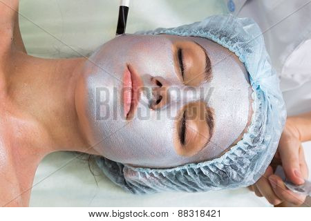 Beautician working on a face model in a spa salon