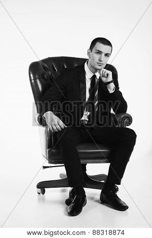 Male businessman sitting on a black leather chair on a white background