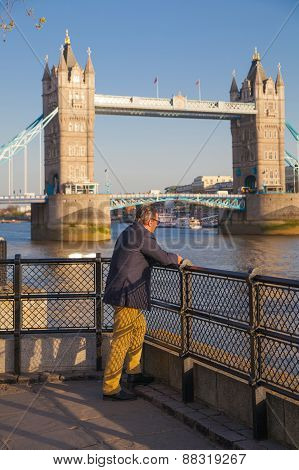 Lonely man in front of Tower bridge in sunset. City of London, south bank of river Thames walk.
