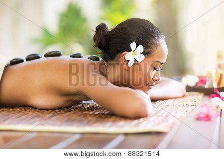 Balinese woman enjoying in hot stone massage in spa salon