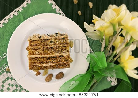 Cake Slice With Nut On Plate. Bouquet Of Yellow Daffodil Or Narcissus With Green Ribbon. Top View.