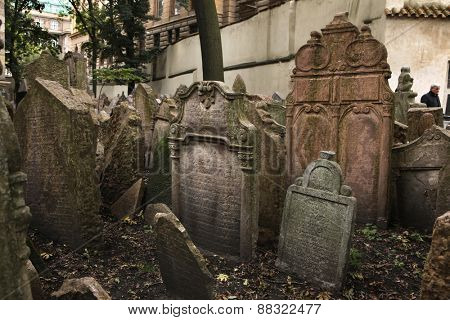 PRAGUE, CZECH REPUBLIC - OCTOBER 15, 2012: Visitor walks among abandoned tombstones at the Old Jewish Cemetery in Prague, Czech Republic.