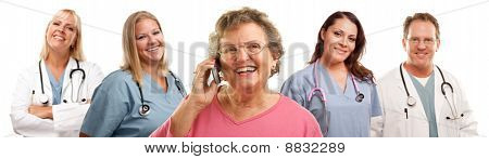 Happy Senior Woman Using Cell Phone And Doctors Behind