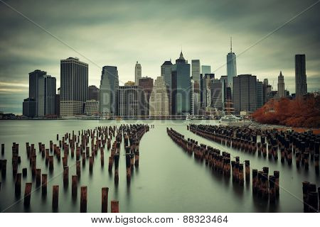 Manhattan financial district with skyscrapers and abandoned pier over East River.