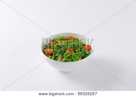 bowl of fresh rucola salad with cherry tomatoes on white background