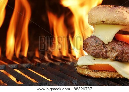 Homemade Cheeseburger Close-up On Flaming Barbecue Grill Background