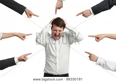 many fingers pointing at screaming stressed businessman. isolated on white background