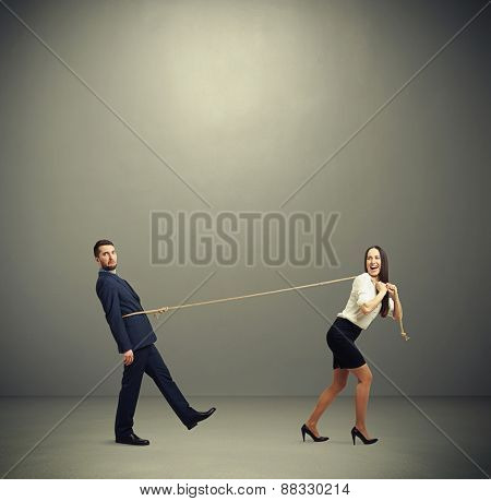 concept photo of henpecked husband. happy laughing woman pulling man on the rope and looking at him. photo in empty grey room