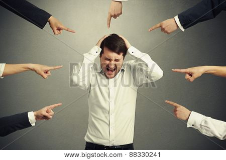 many fingers pointing at screaming stressed businessman in white shirt. photo on dark background