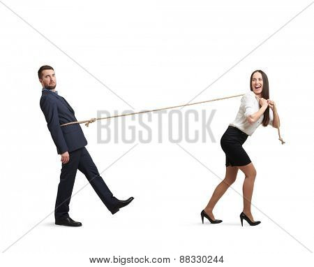laughing woman pulling man on the rope and looking at him. man following the woman and looking at camera with perplexity. isolated on white background