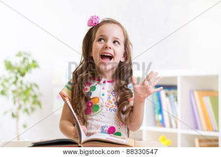 smiling child girl reading book at home