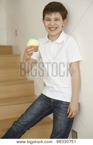 Little boy standing on stairs giving gift cookie to dad, happy big smile.