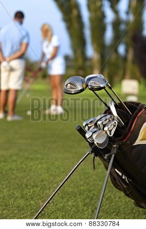 Closeup photo of professional golfing kit on golf course, on green grass.