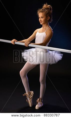 Ballet student in ballet costume practicing by ballet bar.
