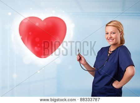 Pretty young nurse healing a red heart