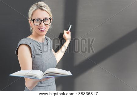 Teacher writing with chalk on blackboard and holding an open book.