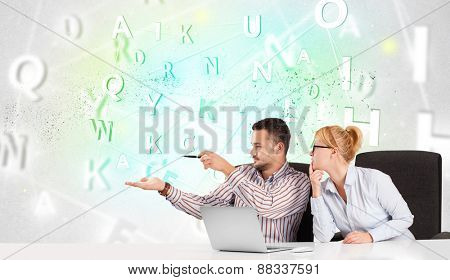 Business people at white desk with green word cloud