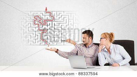 Business persons at desk with labyrinth in the background