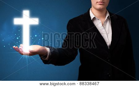 Young businesswoman holding a glowing cross in her hand