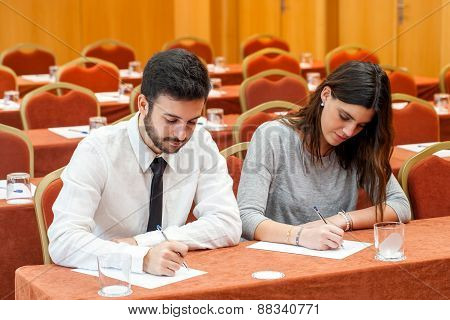 Young Business Couple Taking Notes In Conference Room.