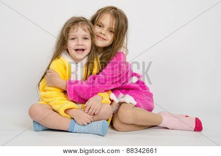 Two Girls Sit In Robes