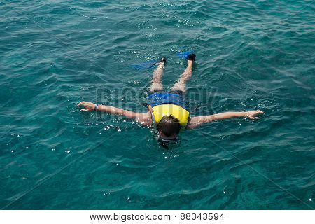 Man Snorkeling In Water With Life Jacket