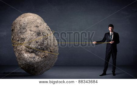 Businessman pulling huge rock with a rope concept on background