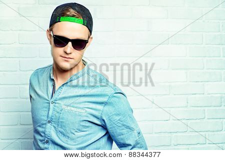 Happy young man in casual clothes and sunglasses posing at studio.