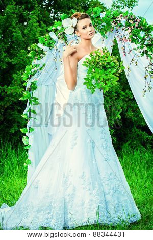 Beautiful elegant bride stands under the wedding arch. Wedding dress and accessories. Wedding decoration.