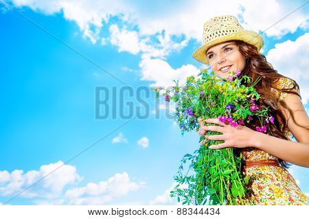 Beautiful smiling young woman standing over blue sky with a bouquet of wild flowers. Summer.