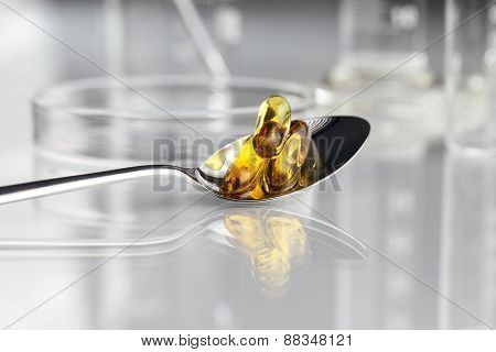 spoon whit vitamins pills omega 3 supplements with petri dish