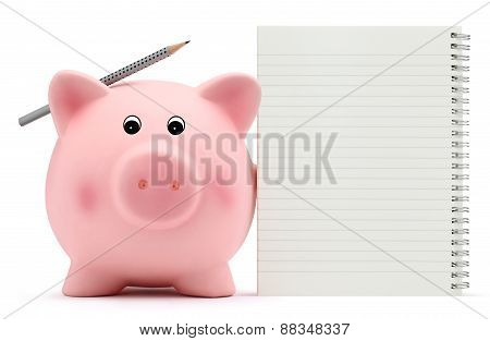 piggy bank with exercise book and pencil on white background