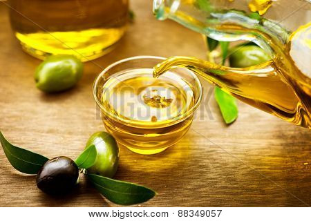 Olive Oil. Bottle pouring Virgin Olive Oil in a bowl close up. Olives and Healthy Olive oil being poured from glass bottle. Diet. Dieting concept. Healthy food