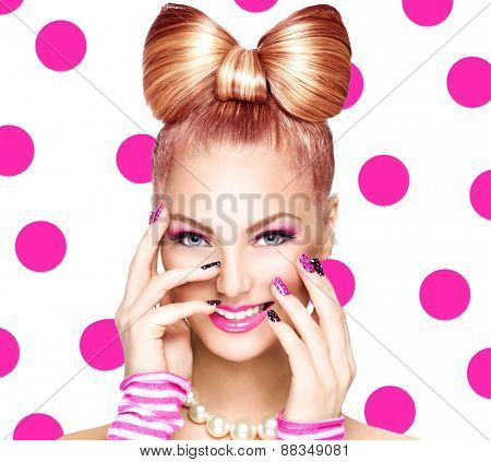 Beauty fashion model girl with funny bow hairstyle, pink nail art and makeup over polka dots background. Colourful Studio Shot of Funny Woman. Vivid Colors. Emotion