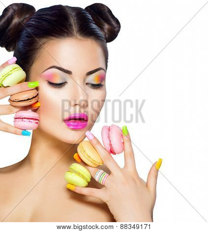 Beauty fashion model girl with colourful makeup and manicure taking colorful macaroons. Beautiful woman, bright make-up. Purple lipstick, vivid eyeshadow and accessories.Diet,dieting concept. Sweets