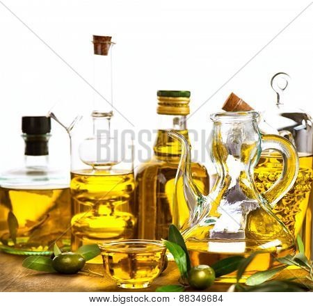 Olive Oil. Bottles and jars of extra virgin olive oil over white background on wooden table. With copy space for your text